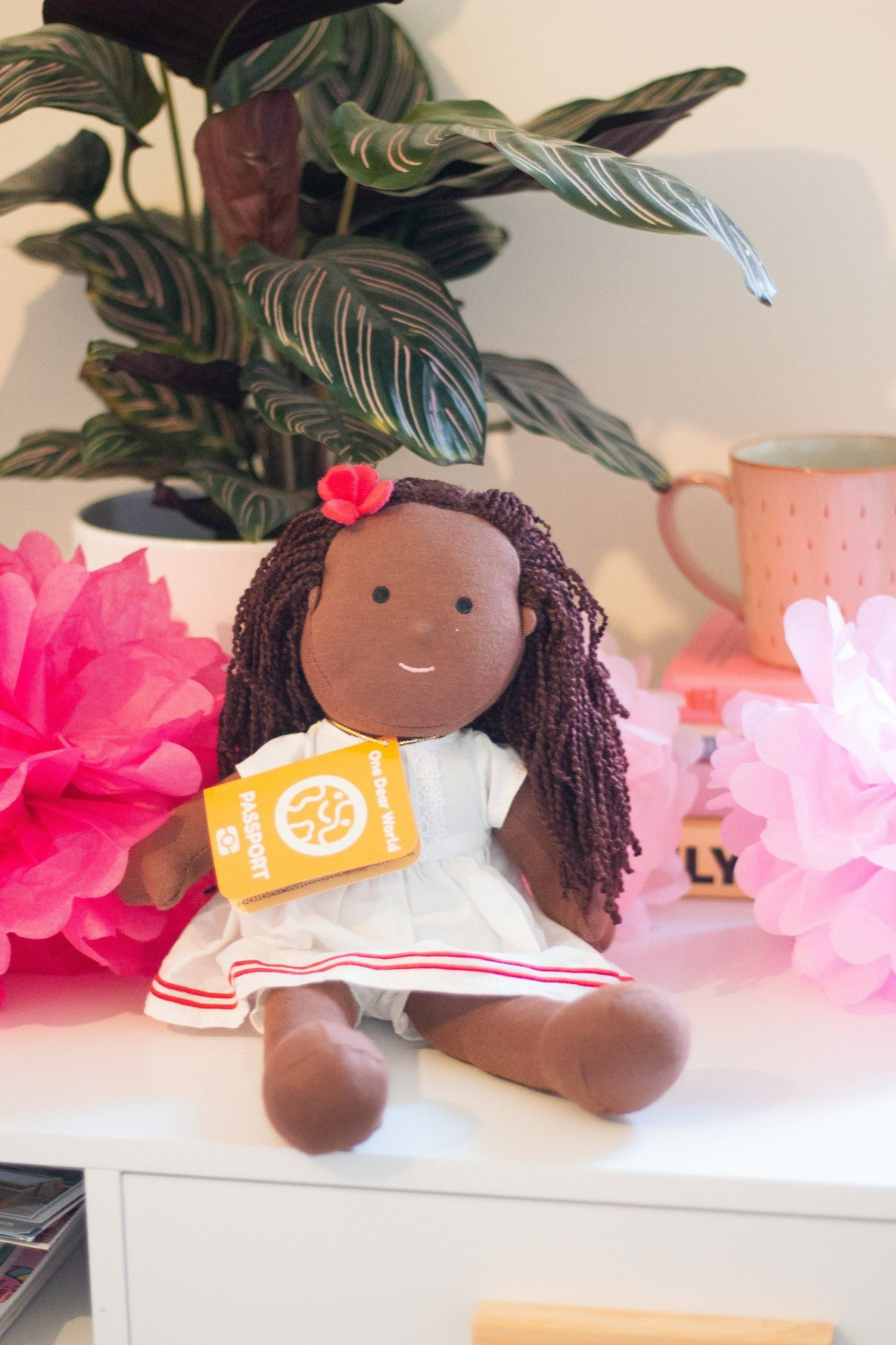 Rag doll with dark skin and dark hair and a little red flower in her hair.