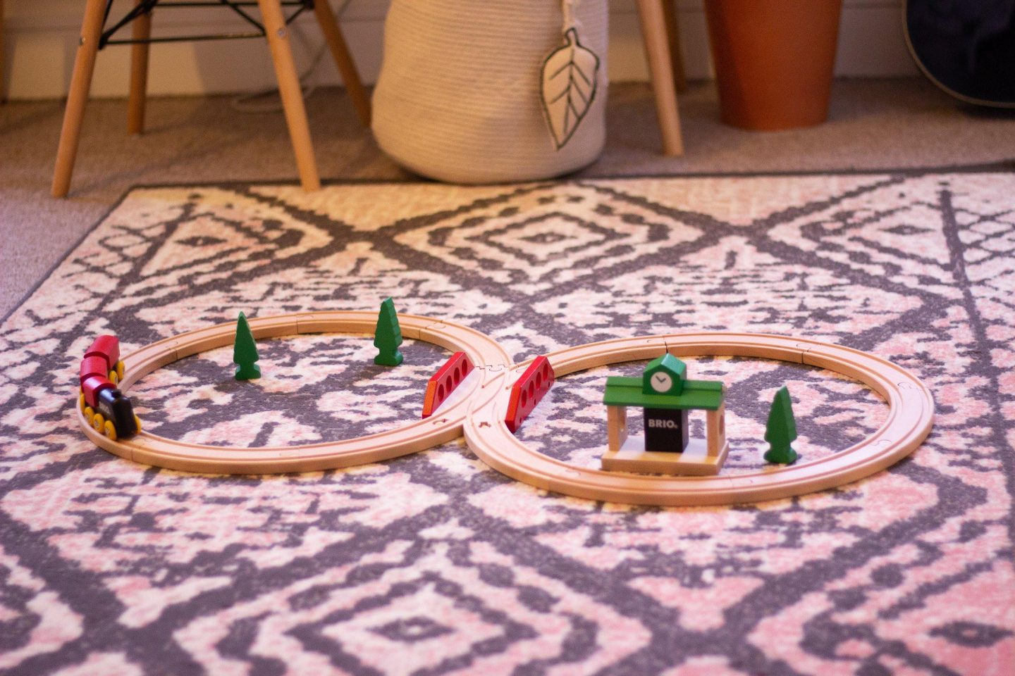 Children's train set on a pink and black aztec rug