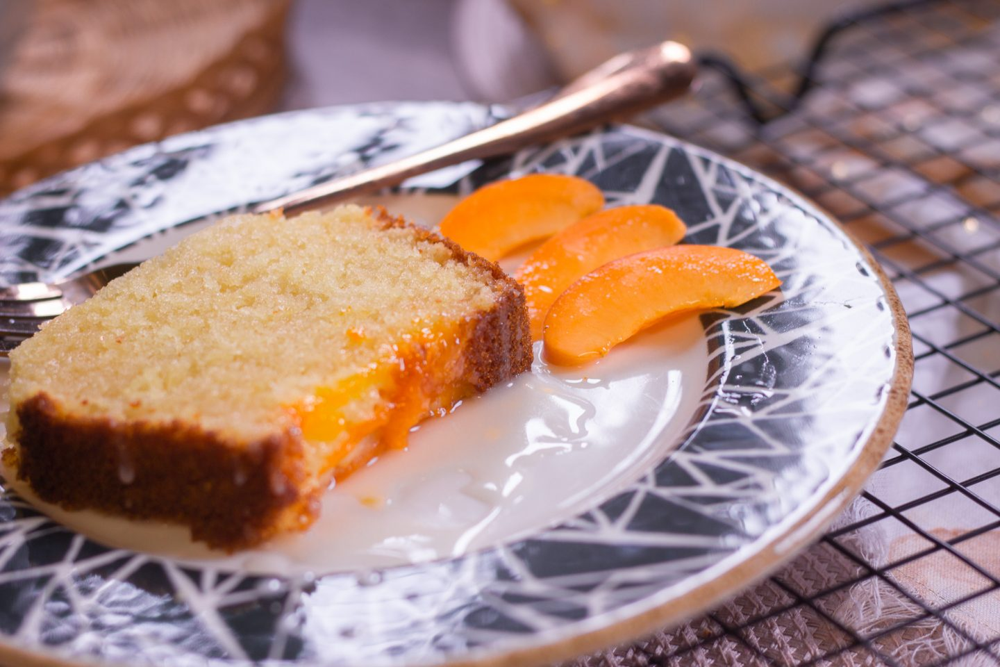 A slice of apricot and honey cake with a sliced fresh apricot as decoration